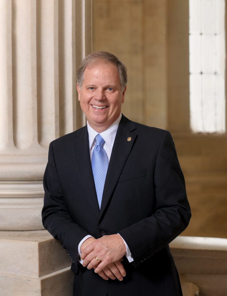 Doug Jones standing by a column